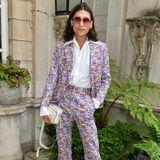 Designer Kyle De'Volle wird in einem lila Anzug mit Blümchenmuster zum Blickfang auf der London Fashion Week. Der Look mit Schlaghose und spitz zulaufenden Lederstiefeln erinnert an die 70er-Jahre.