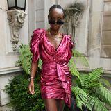 Model Eunice Olumide trägt ein pinkfarbenes Mini.Dress mit Glitzermuster. Kombiniert wird das auffällige Kleid mit schwarzen Schnürstiefeln und einer dunklen Sonnenbrille.