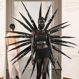Ein Model der Fashion East-Show läuft in einem auffälligen Outfit besteht aus schwarzem Rock, schwarzem Bandeau-Top und großen Stacheln über den Catwalk.