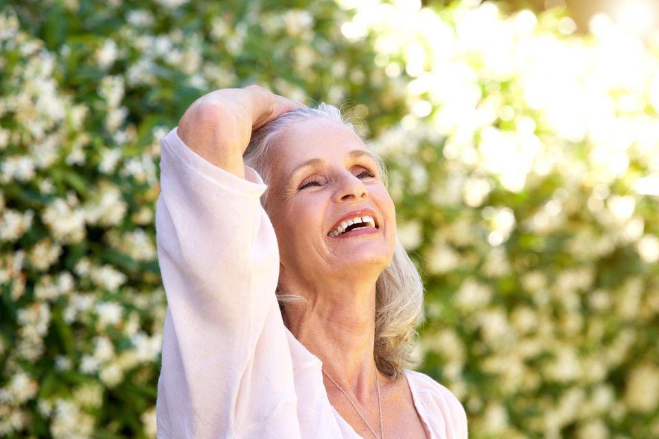 Ältere Frau streift mit der Hand durch die Haare
