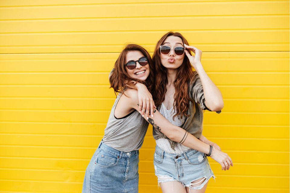 Farbpsychologie + Lieblingsfarbe: Zwei fröhliche Frauen stehen vor einer gelben Wand.