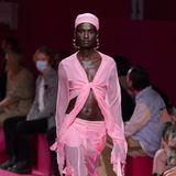 Ob das abgesprochen war? Passend zum rosa Laufsteg trägt das Model der Modenschau von Blumarine ein lustiges Ensemble in rosa Farbe.