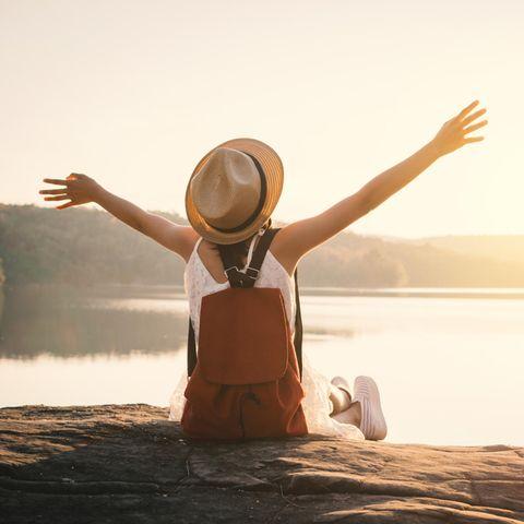Eine Frau sitzt auf einem Stein, schaut in den Sonnenuntergang und reißt die Hände in die Luft vor Freude.