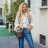 Chiara Ferragni greift für die Fashion Week zu einem besonders stylischen Outfit: Die Designerin trägt eine ausgestellte Hose mit fransigem Saum,schwarze Cowboystiefel und eine weiße Bluse in Kombination mit einer bestickten Weste. Die Haare der Zweifach-Mama sindlässig auf eine Seite gelegt.