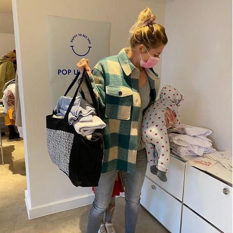 Stars und ihre Einkaufstüten: Nina Bott trägt Einkaufstasche und Baby gleichzeitig