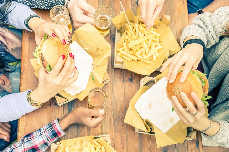 Entzündungsfördernde Lebensmittel: Menschen essen Burger mit Pommes und trinken Bier.