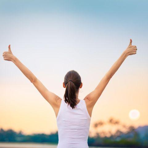 Eine Frau reckt ihre Arme nach oben und zeigt mit ihren Daumen nach oben