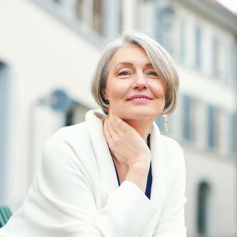 Frau über 50 sitzt auf einer Bank und lächelt