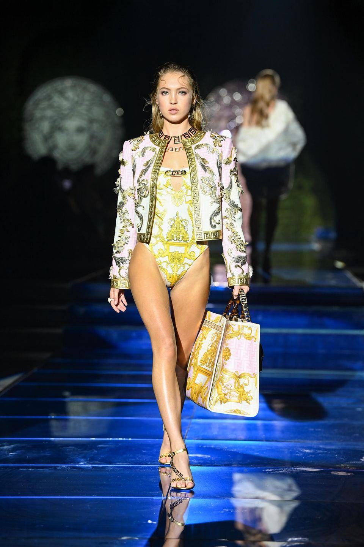 Lila Grace Moss Hack rockt den Laufsteg der Fendi x Versace-Show. Die Tochter von Topmodel Kate Moss trägt einen kurzen Body und eine kurz geschnittene Jacke mit goldenen Verzierungen.