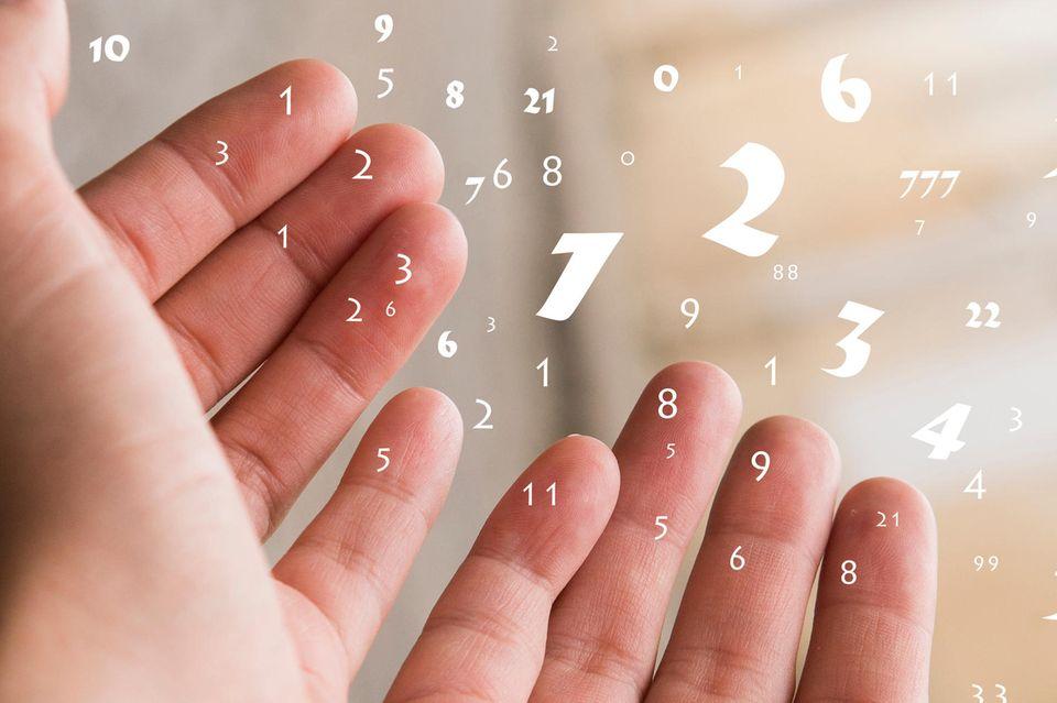 Weiße Zahlen fliegen aus offenen Händen