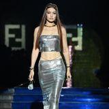 Wer darf bei so einem Event nicht fehlen? Topmodel Gigi Hadid schwebt über den Laufsteg der Fendi x Versace-Show und macht das prominente Aufgebot perfekt. Sie präsentiert einen silberfarbenen Look aus Midi-Rock und kurzem Top.