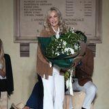 Nach einer erfolgreichen Fashion-Show betritt Designerin Nicoletta Spagnoli den Laufsteg und bekommt einen großen Blumenstrauß überreicht.