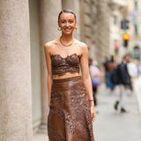 Nataly Osmann zeigt sich in einem monochromen Look: Sie trägteinen braunen Midi-Rock, der mit Lochstickereien verziert wird. Dazu kombiniert sie ein farblich passendes Crop-Top.