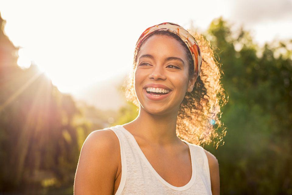 Was die Form Ihrer Augenbrauen über Ihre Persönlichkeit verrät: Junge Frau, die fröhlich lacht