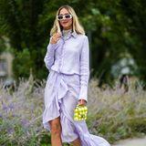 Model Candela Novembre trägt eine lilafarbene Bluse mit Rüschen und farblich passenden Rock mit verspieltem Schnitt. Abgerundet wird der Look durch schwarze Loafer und einer Mini-Bag mit kariertem Muster.