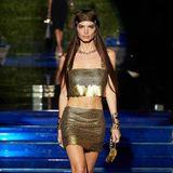 Bei der Modenschau vonFendi x Versace läuft auch Emily Ratajkowski über den Laufsteg. Das Model trägt einen goldfarbenen Minirock mit dazugehörigemkurzen Top.