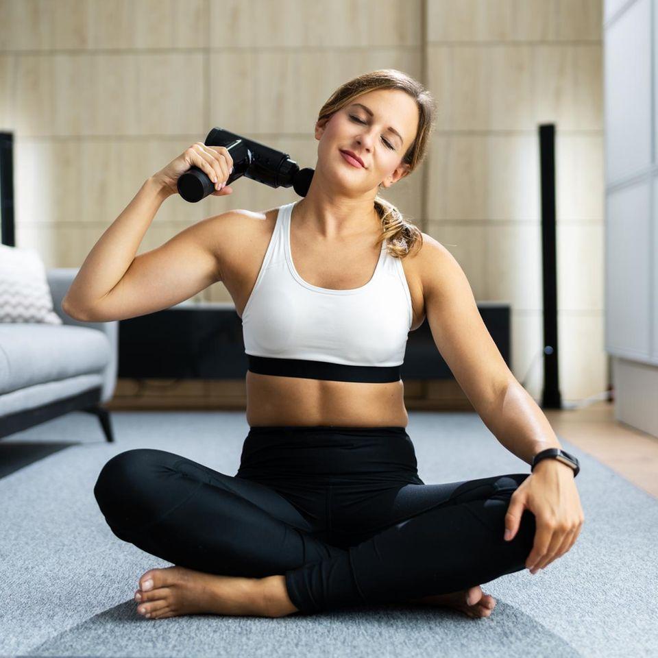 Massagepistole-Test: Die besten 8 Modelle, Frau sitzt auf dem Boden und benutzt eine Massagepistole