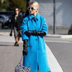 Caro Daur ist eine eche Trendsetterin und in den Modemetropolen dieser Welt zu Hause. Bei der Fashion Week in Mailand besuchtsie die Frühjahr/Sommer 2022-Show von Prada. Passend zum Anlass greift die Influencerin zu einer Henkeltasche des italienischenLabels. Durch einenblauen Mantel und schwarzen Lederhandschuhen wird der Look abgerundet.