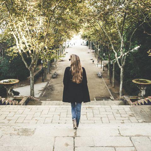 Wie Sie gehen, verrät einiges über Ihren Charakter: Frau geht Treppen im Park herunter.