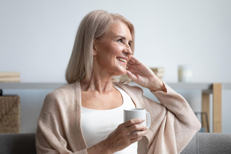 Frauen ab 50: Ältere Frau sitz auf Sofa und trinkt Tee