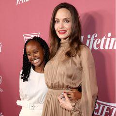 """Angelina Jolie und TochterZahara Jolie-Pitt zeigen sich beim """"Variety's Power of Women""""-Event in Beverly Hills als stylisches Mutter-Tochter-Duo. Aber diesmal fällt Zahara mit ihrem Lässig-Look in Weiß deutlich mehr ins Augeals Mama Angelina im hellbraunen, seidigen Retro-Style."""