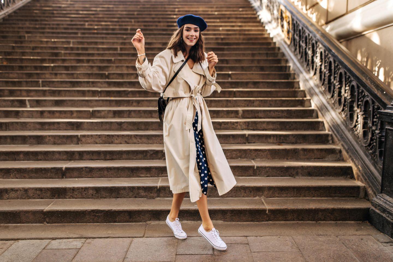 Trenchcoat Trend 2021: Die schönsten Mäntel, Junge französische Frau mit Trenchcoat