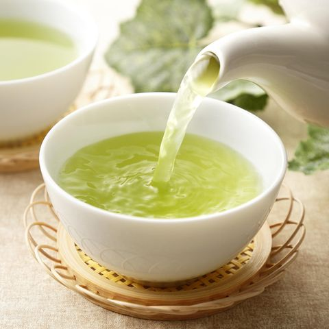 Grüner Tee wird in einen weißen Porzellanbecher eingegossen.