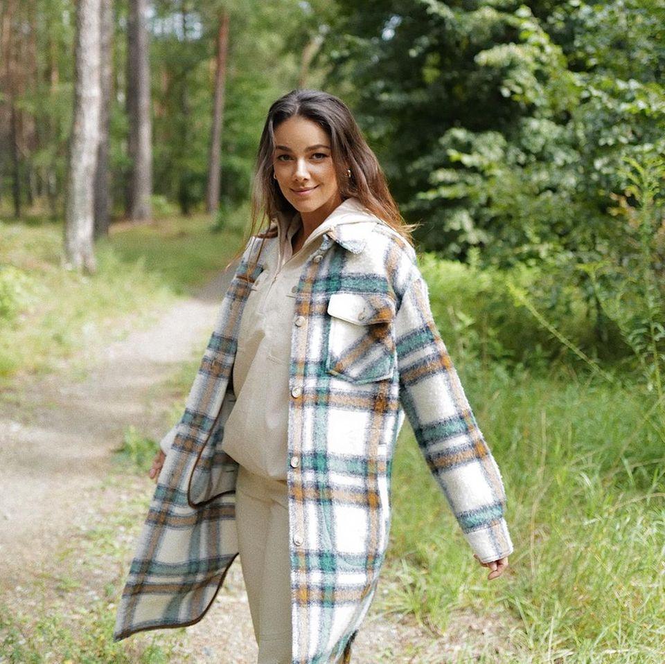 Janina Uhse posiert im Wald für ein Foto.