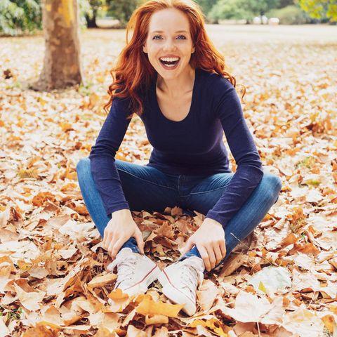 Wochenend-Horoskop ab 1.10.2021: Rothaarige Frau sitzt lachend im Laub