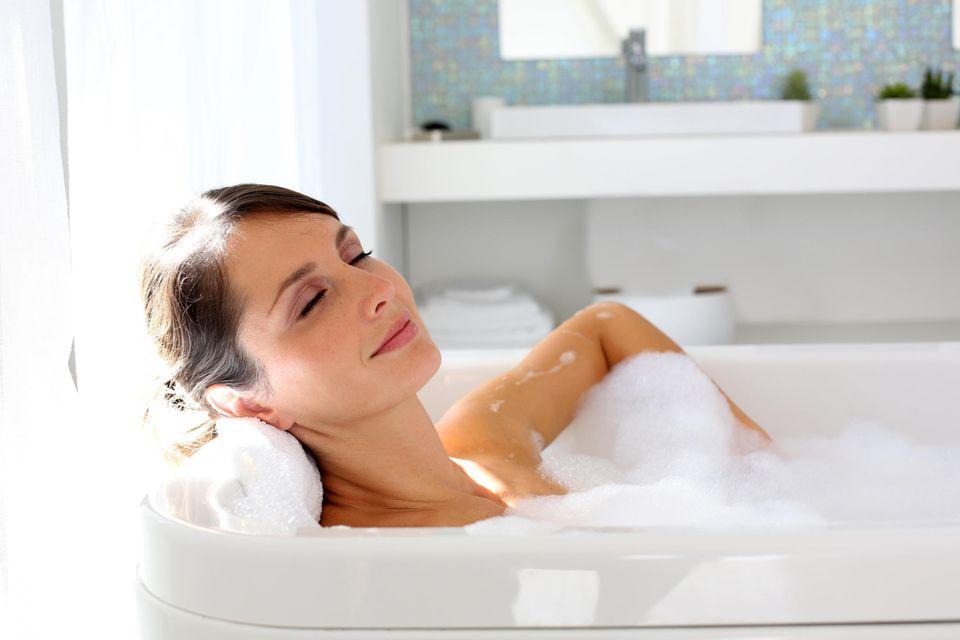 Badebomben: Frau liegt in Badewanne mit viel Schaum und entspannt