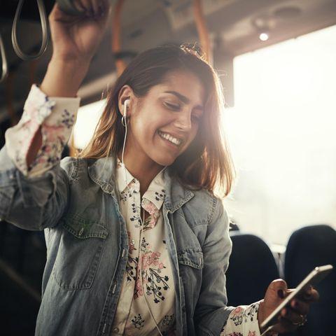Musikgeschmack & Persönlichkeit: Frau hört im Bus Musik auf dem Smartphone.