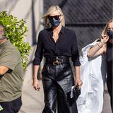 Charlize Theron beweist in hochbündigem Leder-Look zur schwarzen Bluse, dass sie genau weiß, wie lässiger Streetstyle funktioniert.