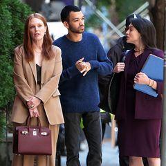 """Bei ihren Dreharbeiten für ihren Apple TV+Film """"Sharper"""" zeigt sich Julianne Moore ganz businessmäßig am Set: Sie trägt einen hellbraunen Powersuit mit schwarzen Pumps und passendem schwarzen Top. Dazu kombiniert die Schauspielerin eine dunkelrote Birkin Bag. Ein Power-Look für eine Powerfrau!"""