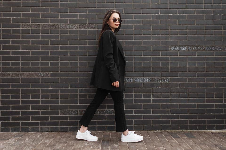 Persönlichkeit: Was Ihre Lieblings-Sneaker über Sie verraten – Frau trägt weiße Sneaker zu schwarzem Outfit.