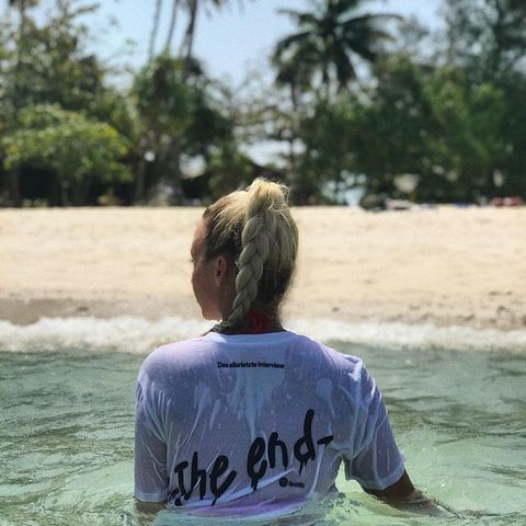 Visa Vie badet mit T-Shirt im Wasser und schaut Richtung Strand.