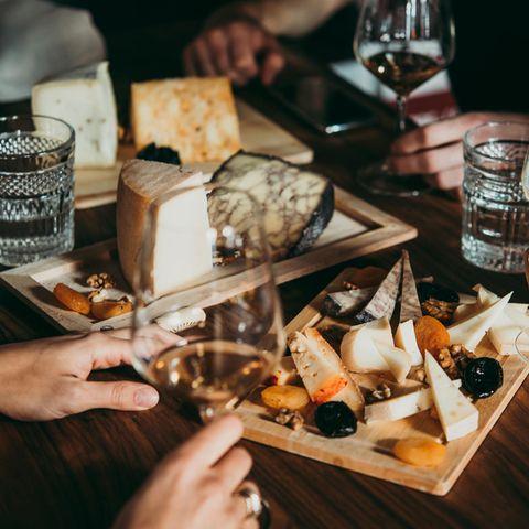 Zu viel Käse: Auf dem Tisch steht ein Brett mit verschiedenen Sorten Käse. Dazu gibt es Wein.