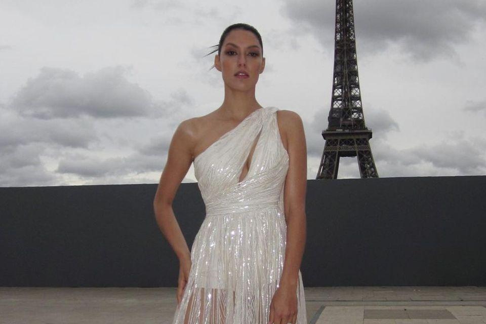 Rebecca Mir posiert vor dem Eiffelturm.