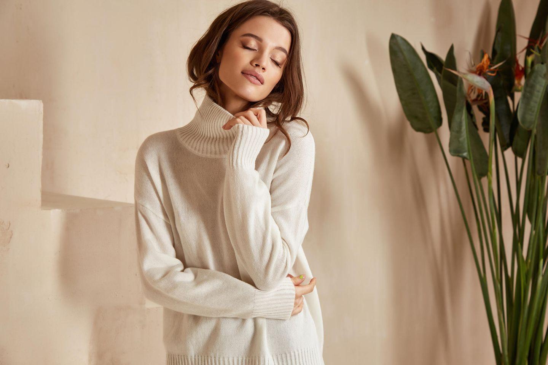 Pullover Trend 2021: Die schönsten Pullis, Junge Frau hat die Augen geschlossen und lächelt