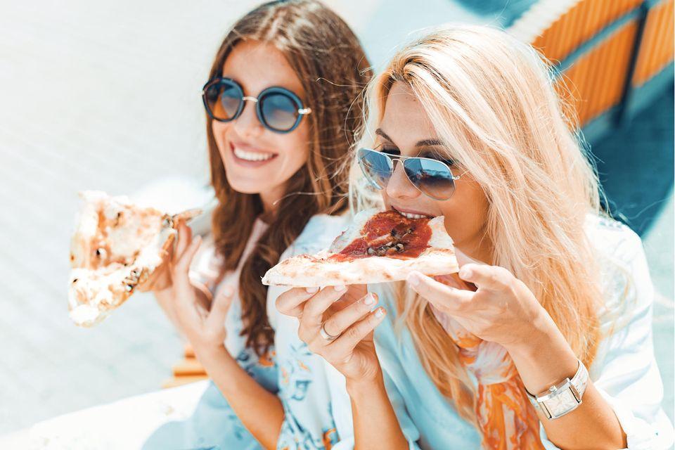Diese 7 Angewohnheiten können Ihrer Darmflora schaden: Frauen essen Pizza.