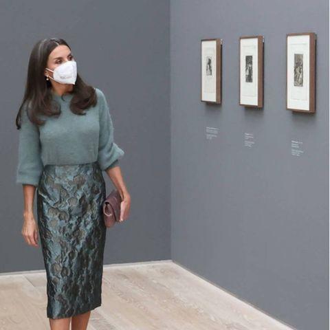 """Für die Eröffnung der Ausstellung """"Goya"""" in Basel wählt Königin Letizia einOutfitmit Trend-Potential. Der weiche Wollpullover mit Trompetenärmeln und der leicht gemusterte Pencil Skirt kommen in angesagtem Graugrün daher und bilden in Kombination mit den grauen Accessoires den perfekten Monochrome-Look."""