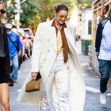 Gigi Hadid, auffällig wie immer! In einem creme-weißen Mantel huscht die Modelmamadurch New York City. Sie kombiniert den zweireihigen Mantel mit gedeckten Farben, wobei Gigis Sonnenbrille den aus den 70ern inspirierten Look vervollständigt.