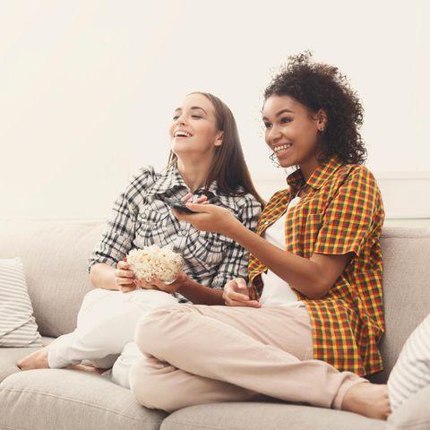 Was Ihre Lieblingsserie über Ihren Charakter enthüllt: Zwei Frauen schauen lachend Fernsehen.