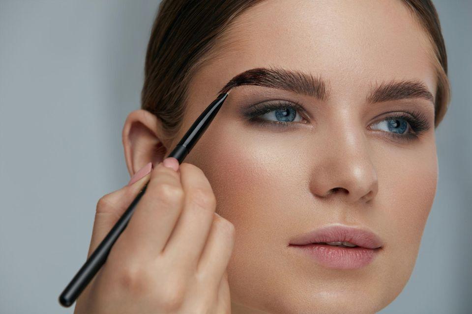 Eine Frau färbt sich die Augenbrauen mit permanenter Farbe