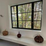 Statt auf klassische Kürbisse setzt Ashley Tisdale in ihren eigenen vier Wänden auf kunstvolle Kürbisse aus Holz. DiesesTrio ist ein absoluter Blickfang: Die Schauspielerinplatziert sie direkt unter ein Fenster mit Aussicht auf herbstliche Bäume und Laub.