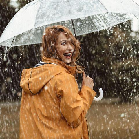 Frau läuft mit dem Schirm durch den Regen