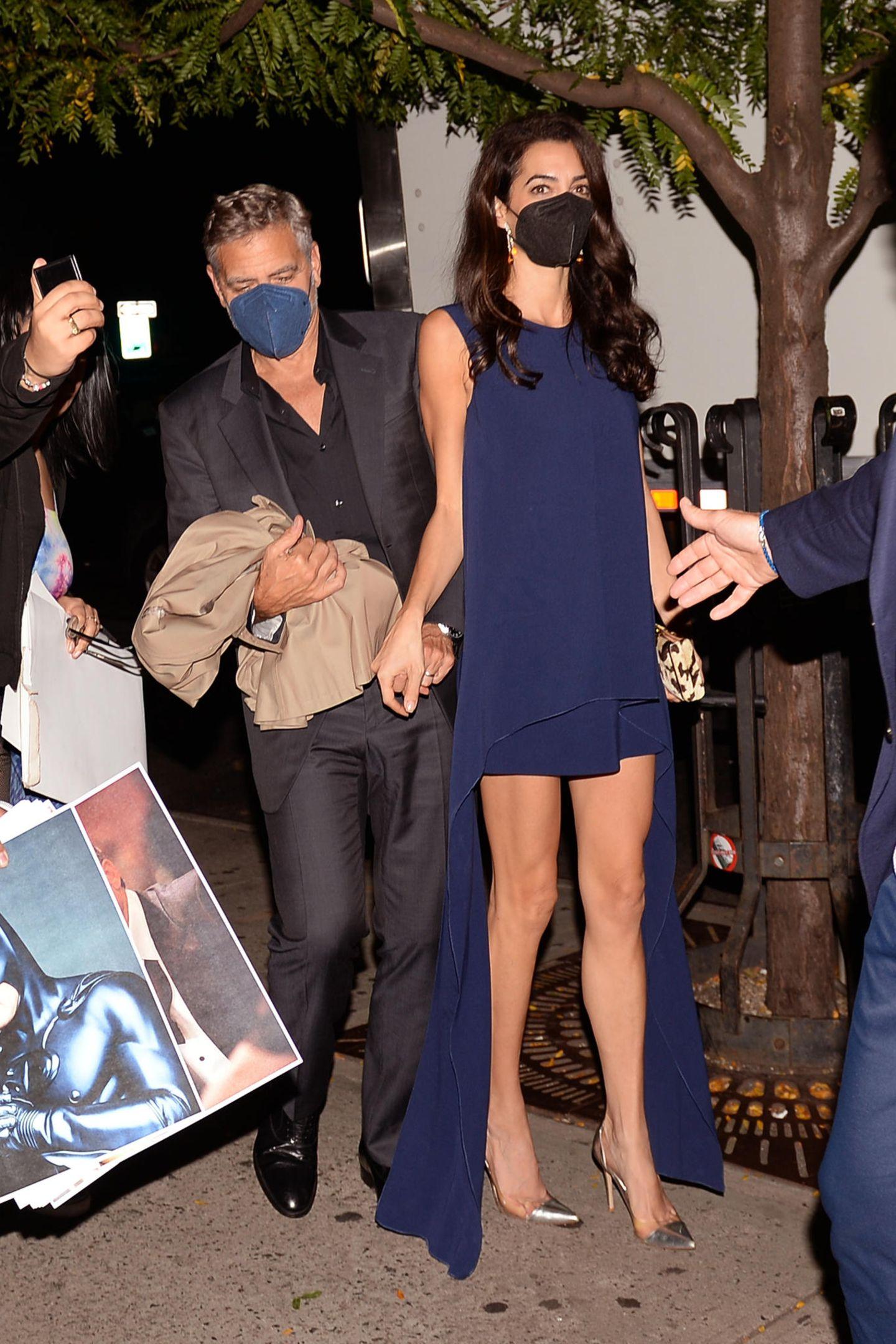 Amal Clooney gehört zu den bestgekleideten Frauen der Welt. Die Anwältin ist bekannt für ihren eleganten und zeitlosen Stil. Das stellt sie einmal mehr bei einemDatenmit Ehemann George Clooney unter Beweis. Hier zeigt sie sich in einem dunkelblauen Minidress mit seitlichen Schleppen. Dazu kombiniert sie goldfarbene Heels und eine Farbe im gleichen schimmernden Ton.Ein Outfit, das auf den ersten Blick schlicht wirkt, aber mit ganz besonderen Details begeistert.