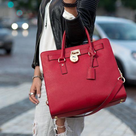 Wie Sie Ihre Handtasche tragen, verrät einiges über Ihren Charakter: Frau trägt rote Tasche