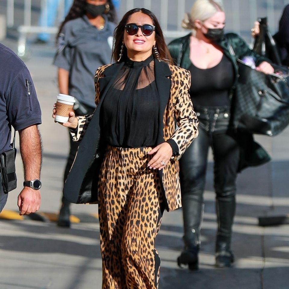 Salma Hayek läuft mit einem Kaffee in der Hand auf dem Bürgersteig.