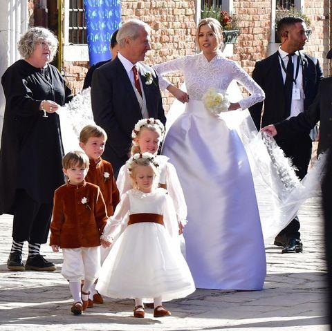 """Géraldine Guyot undAlexandre Arnault, der zweitälteste Sohn von """"LVMH Moët Hennessy""""-Milliardär Bernard Arnault, feiern in Venedig ihre große Hochzeitsfeier. Bereits vor drei Monaten hatten die zweisichdas Jawort in Paris gegeben. Wie es einer Millionen-Hochzeit gebührt, fällt das Hochzeitskleid entsprechend glamourös aus. Das Brautkleid, bestehend aus Spitzenoberteil undeinem Rock aus dickemSeidenstoff, erinnert starkan das Brautkleid von Grace Kelly, das sie trug,als sie Fürst Rainier ehelichte."""