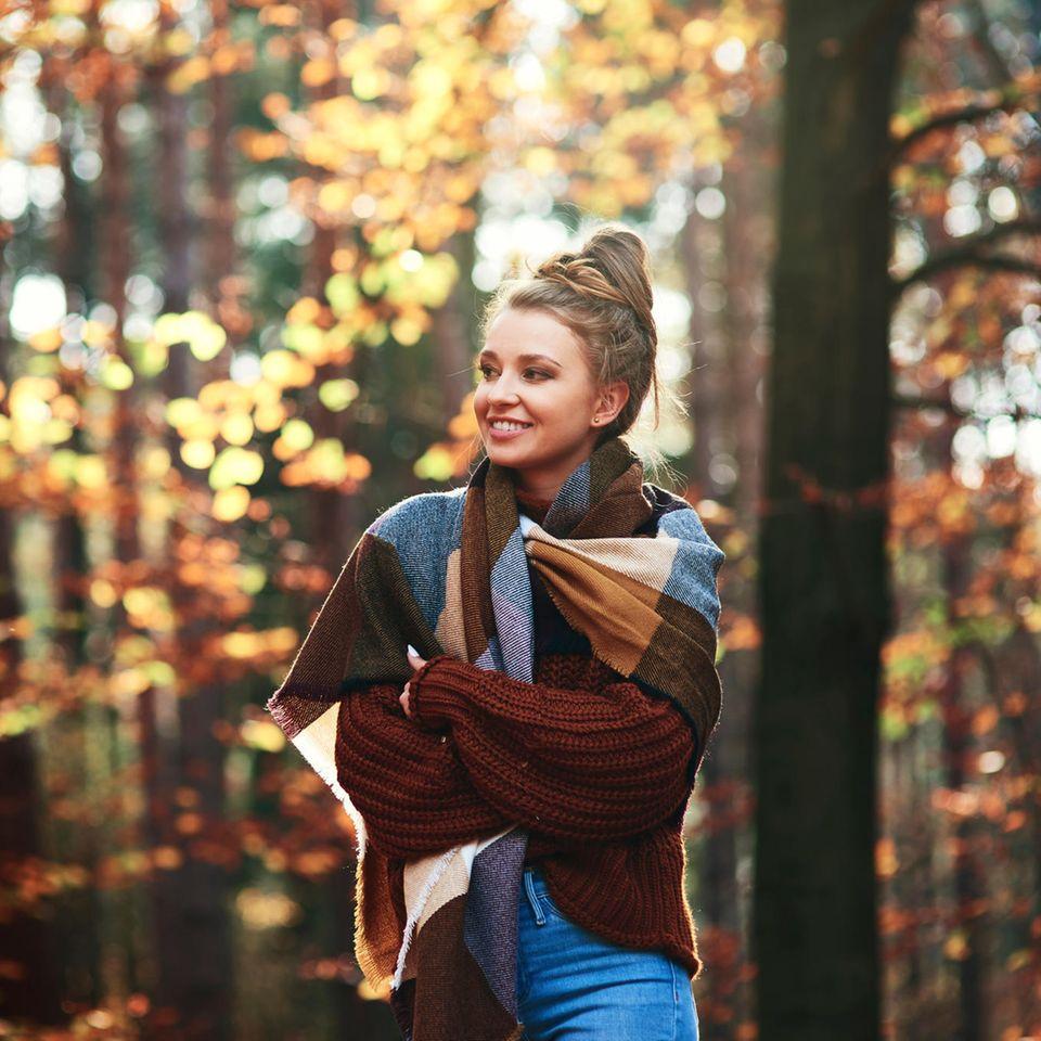 Eine Frau mit einer Decke um ihren Oberkörper steht lächelnd im Wald